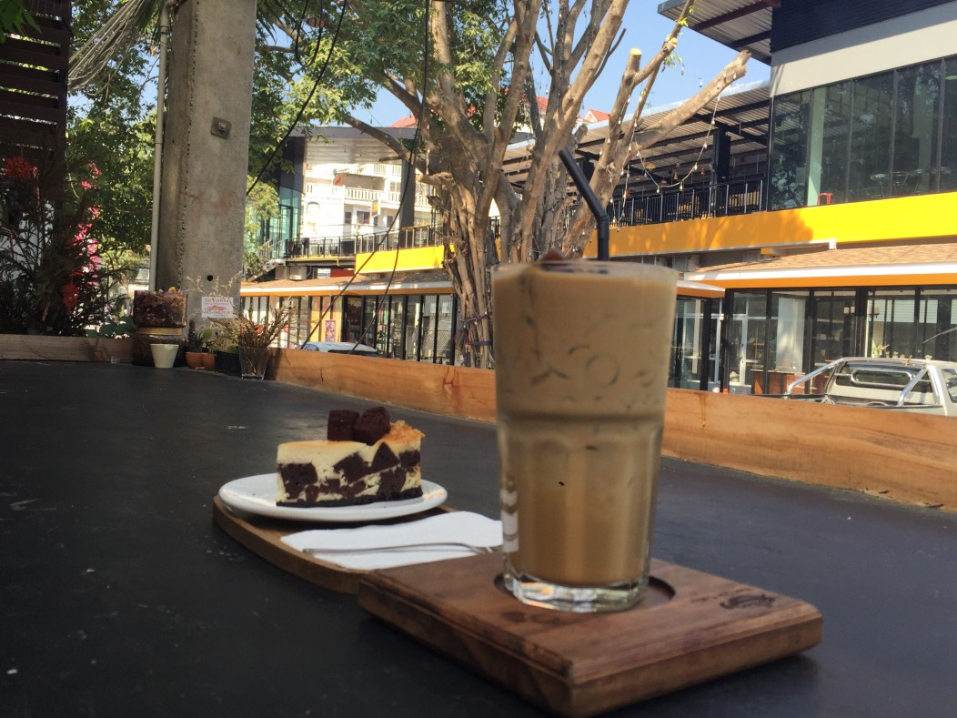 Coffee and brownie cheesecake at an outdoor cafe on Nimmanhaemin Road in Chiang Mai, Thailand.