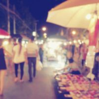 Blurred photo of a Thai walking street and market.