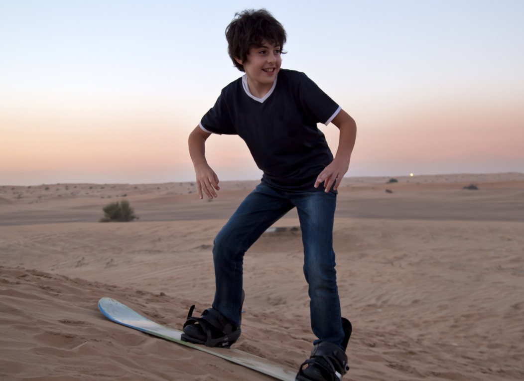 A boy sandboarding on a sand dune in the desert at dusk.