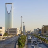 A downtown photo of King Fahd road in Riyadh Saudi Arabia. The highway and buildings look quite modern and the KingDom Tower can be seen in the background.
