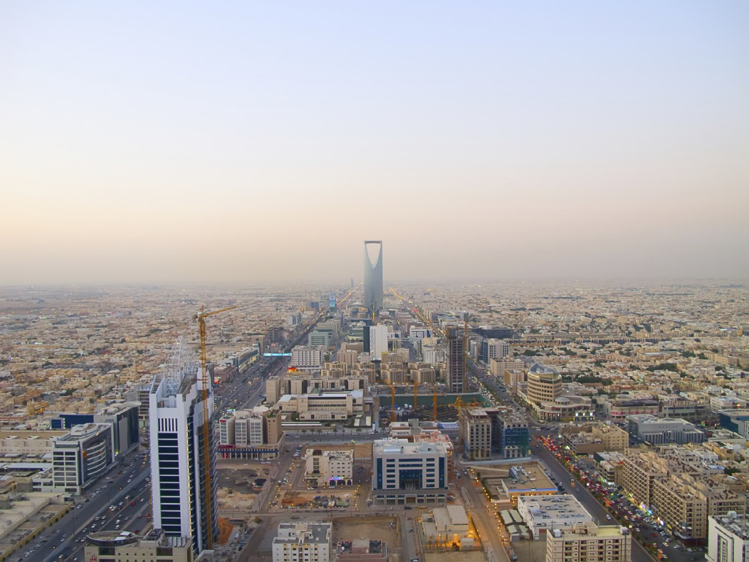 A panoramic cityscape of Riyadh, capital city of Saudi Arabia. A fine haze hangs over the city during twilight. The buildings looks simple, yet modern.