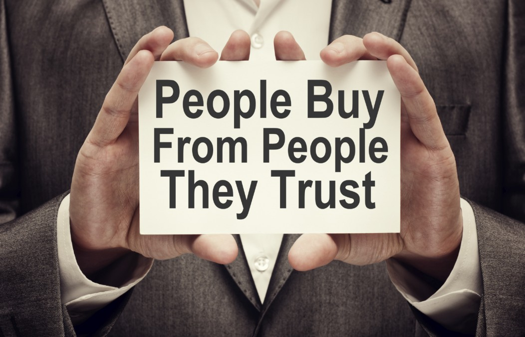 A sign held by two hands which readS: People Buy from People They Trust.