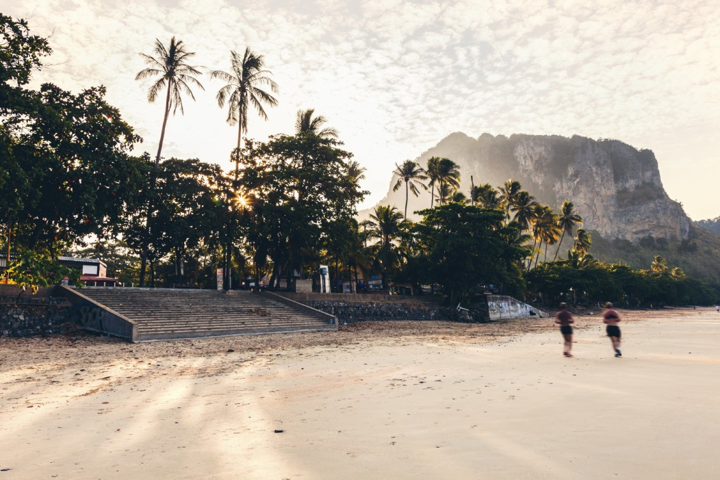 A gorgeous beach in Mauritius. Limestone mountains can be seen in the background and tall palms in the foreground. A couple are jogging on the beach.
