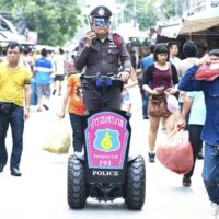 Thai police officer patrolling a local market in Bangkok Thailand.