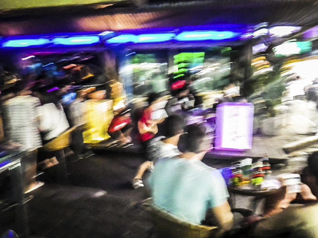 Defocused photo of a bar in Thailand. Many expats are seated and bar neon lights surround them.