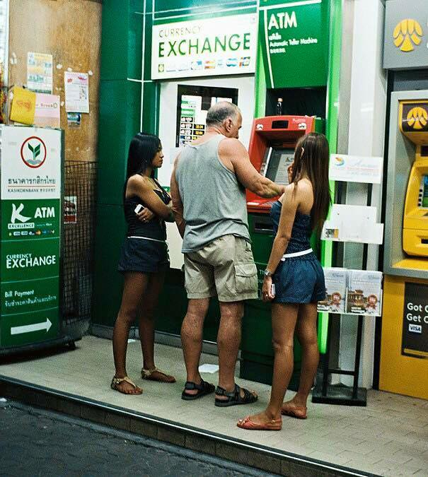 Old sexpat man at an ATM machine withdrawing money. Two bargirls stand beside him, looking at the ATM.