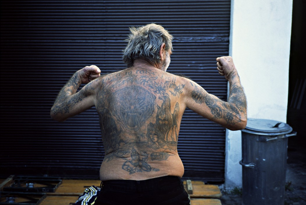 Tattooed old ex con showing off his back tattoos in an alley in Vietnam.