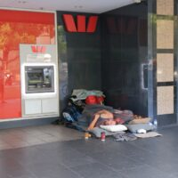 Two homeless US expats sleeping beside a foreign ATM machine.