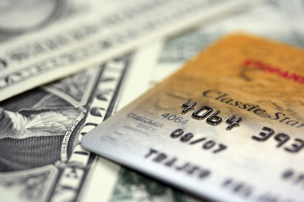 Picture of cash and a credit card. The cash in the background is defocused.