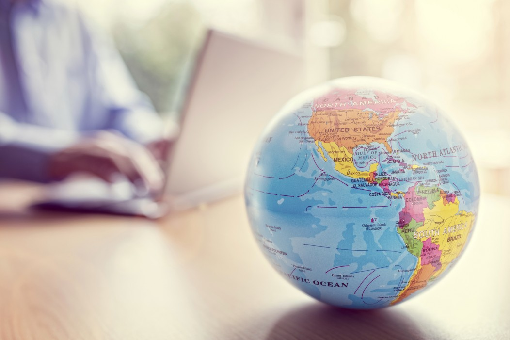 A globe resting on a table with a digital nomad and his laptop defocused in the background.