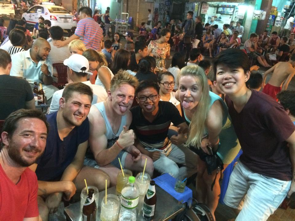 Friends drinking on Bui Vienh street in Ho Chi Minh City, Vietnam. They are posing for pictures; both foreigners and local Vietnamese.