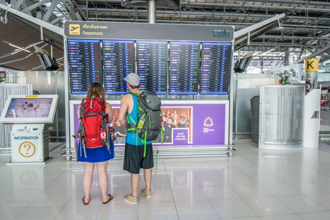 Two backpackers staring at the departures screen in Suvarnabhumi airport in Bangkok, Thailand.