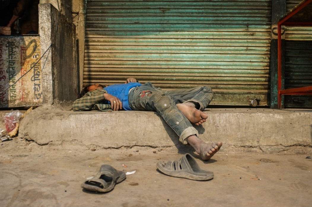 An Indian man passed out on a dirty street in India.