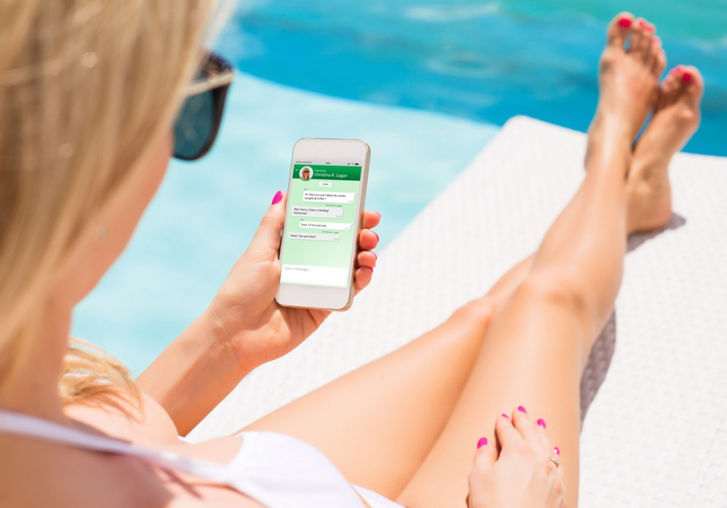 A woman chatting on her smartphone from the convenience of her poolside.