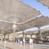Huge, white unbrellas at the An Nabawi Mosque in Medina, Saudi Arabia. Pilgrims walk in the shade underneath.