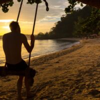 A man on a swing during the sunset at Ao Nang Beach in Thailand. The golden hue is idyllic and exemplifies living in paradise.