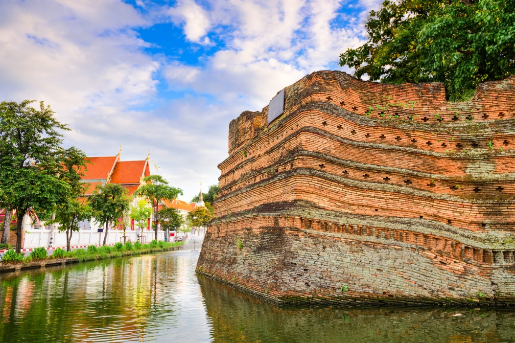 Moat and fort in the old city of Chiang Mai. Temple in the background.