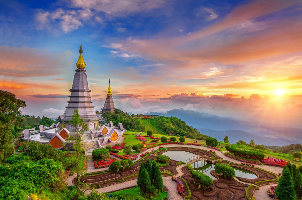 A beautiful temple overlooking the rolling hills near Chiang Mai during a colorful sunset.