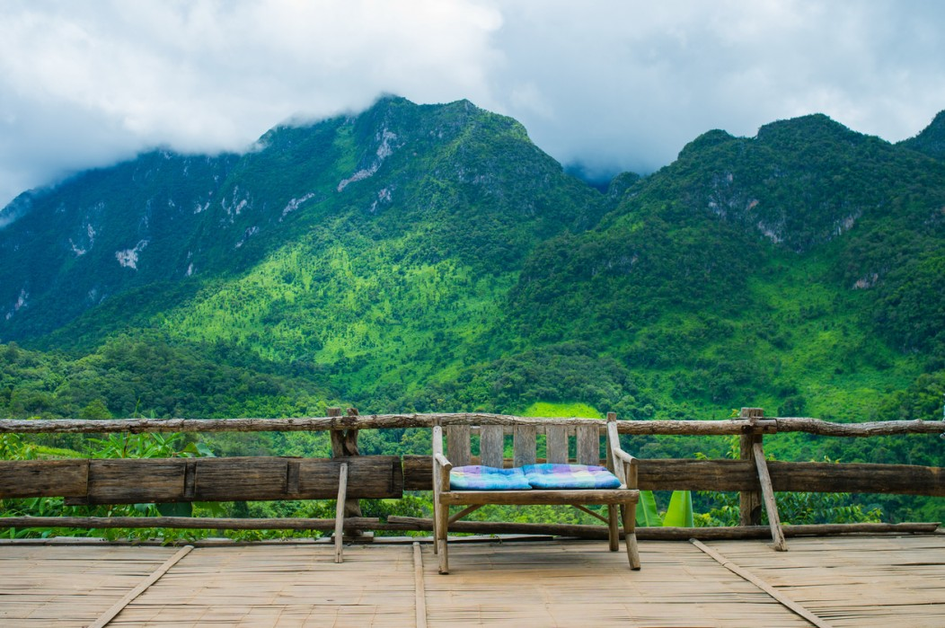 A bench and a serene backdrop of mountains in Chiang Mai, Thailand.